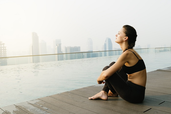 Relaxed young yoga woman in yoga pose near pool. Yoga Concept.